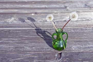green glass vase and dandelion seeds