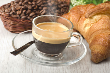 coffee in glass cup with croissants and coffee beans