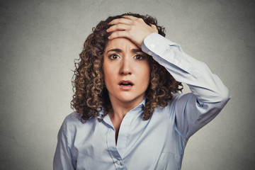 terrified young business woman looking shocked grey background