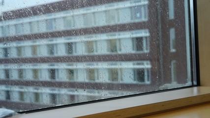 Hagel prasselt an die Fensterscheibe