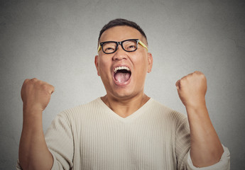 successful student with glasses man winning, fists pumped