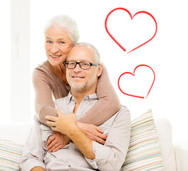 happy senior couple hugging on sofa at home