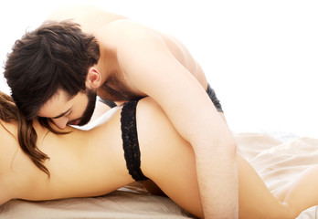 Couple having foreplay in bedroom.
