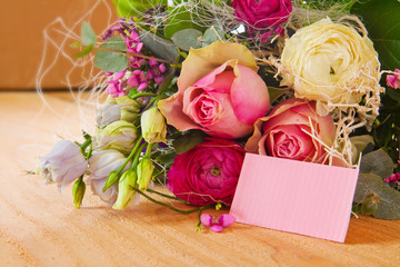 A bouquet of flowers and blank card for text.
