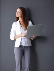 Young woman holding a laptop, standing on grey background