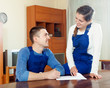 Teamwork of happy workers in uniform looking financial documents