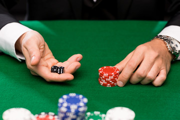 poker player with dice and chips at casino