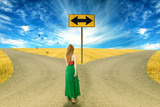 Young woman standing in front of two roads making a choice