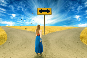 Young woman standing in front of two roads arrow sign