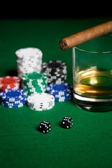 close up of chips, dice, whisky and cigar on table