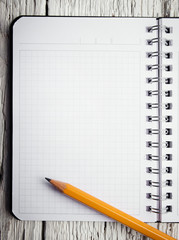 Open blank notepad with empty white pages laying on a wooden tab