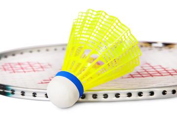 One shuttlecock lying near the badminton racket