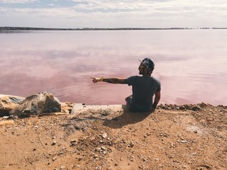 Man shows direction while sitting near the lake with pink water