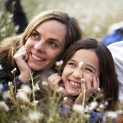 Madre e hija tumbadas en la hierba mirando el cielo