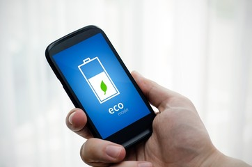 Man holding phone with eco battery mode on display