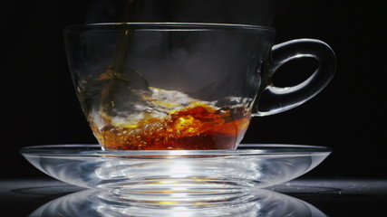 Hot tea being poured into a clear glass cup in slow motion