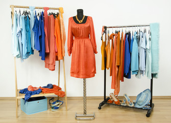 Wardrobe with complementary colors orange and blue clothes.