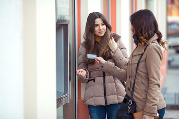 Two young women picking money from ATM