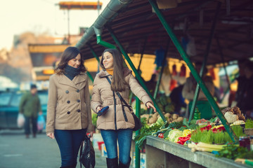 Young girls buying fresh organic food on the market