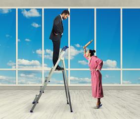 dissatisfied man standing on stepladder