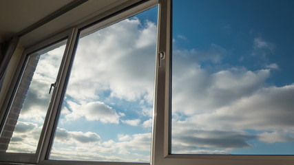 Clouds seen through large, domestic windows.