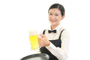 ビールを運ぶ笑顔のウェイトレス