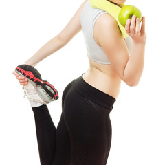 Fitness young woman in running shoes holding apple