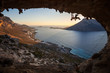 Rock climber climbing on roof in cave, his partner belaying