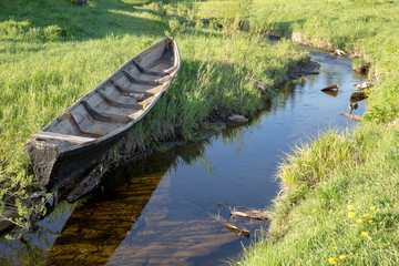 Wooden boat on bank of creek