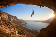 Rock climber hanging on rope while lead climbing before sunset