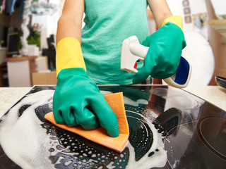 Woman cleaning stove in kitchen