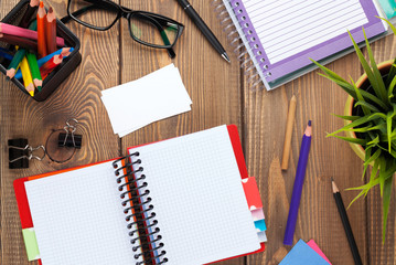 Office table with blank notepad and supplies
