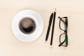 Office desk with coffee cup, supplies and glasses