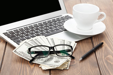 Office table with pc, coffee cup, glasses and money