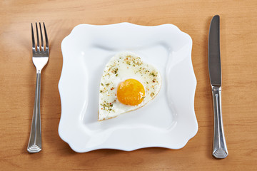 Fried eggs in a heart shape on a white plate and cutlery