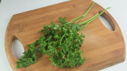 Preparing various fresh herbs on a cutting board.