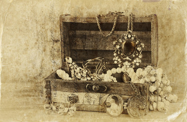 A collection of vintage jewelry in antique wooden jewelry box. r
