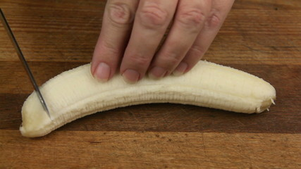 Slicing a fresh banana on a wooden cutting board.