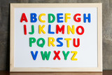 Fototapety Magnet plastic alphabet on whiteboard on cement wall background