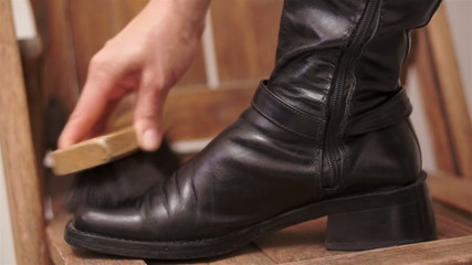 Woman Brushing Her Black Boot