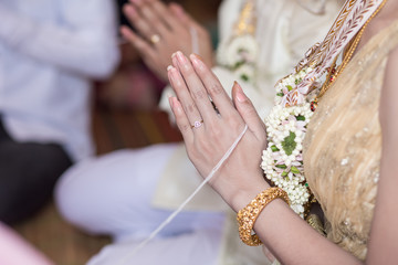 Thai groom wearing wedding ring for his bride
