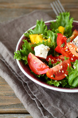 Salad with tomatoes, cheese and greens in a bowl on napkin
