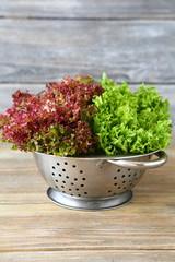 Healthy salad in a colander on wooden boards