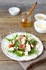 Crispy salad with pears, arugula and figs on a white plate