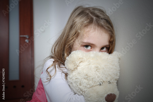 Young sad girl huging a teddy bear - 76348290