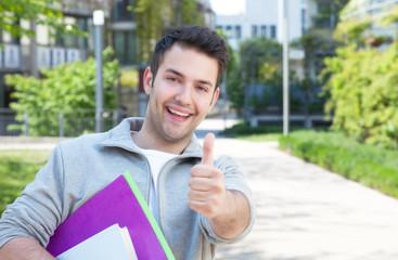 Lachender Student mit Unterlagen auf dem Campus