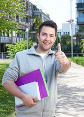 Fröhlicher Student auf dem Campus zeigt den Daumen
