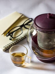 tea cup and teapot with notebook background