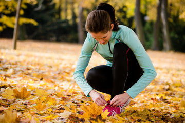 Woman tying shoelaces - jogging in nature