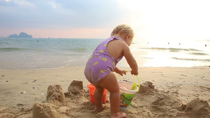 small baby girl in purple swimsuit put the bucket on send and fa